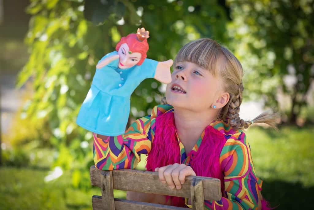girl telling story with puppet summer activities